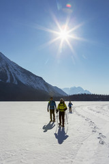 Group snowshoeing on snow covered mountain lake with sunburst and blue sky; Field, British Columbia, Canada