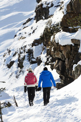 Two female hikers along a snow covered trail and snow covered rock cliff; Lake Louise, Alberta, Canada