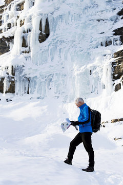 Male hiker on snow covered trail looking at map with a rock cliff covered in ice; Lake Louise, Alberta, Canada