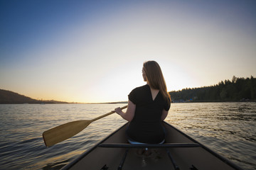 A young woman canoeing at sunset; Vancouver, British Columbia, Canada
