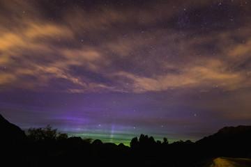 Stars and the Northern Lights (Aurora Borealis) shine through high clouds over Pitt Lake; British Columbia, Canada