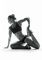 Athletic young woman doing stretching fitness exercise, isolated. Intense stretch pose