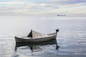 A boat floating on the tranquil Aegean Sea with a ship in the distance; Thessaloniki, Greece
