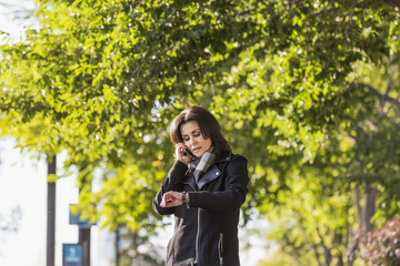 Mature businesswoman talking on her cell phone and checking the time while walking in an urban park outdoors in autumn; Edmonton, Alberta, Canada