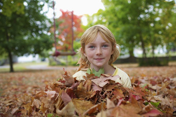 Young girl sitting in pile of leaves in autumn; Picton, Ontario, Canada