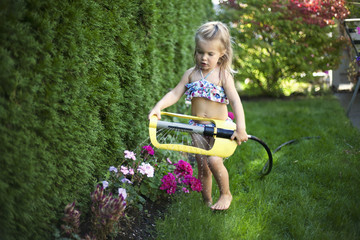 A young girl enjoying the sprinkler on a hot day; Surrey, British Columbia, Canada
