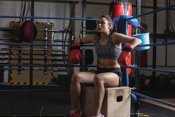 Tired female boxer taking a break after a practice