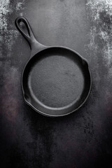 cast iron pan on black metal culinary background, view from above