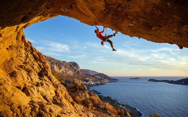 Male climber on overhanging rock against beautiful view of coast below  Fotoväggar