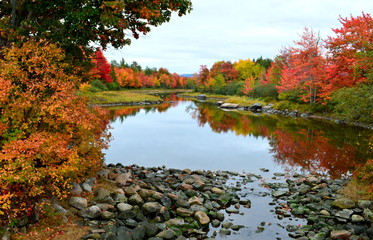Colorful autumn landscape with leaves turning red and reflection of colorful trees in water somewhere in Maine-USA