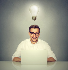 Smiling man in front of computer with light bulb over head