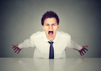 Angry young business man screaming