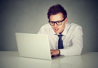 Man using his laptop computer sitting at table