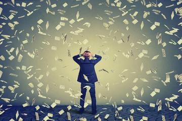 Business man facing wall under money rain .