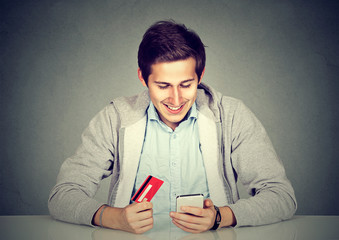 Man holding credit card using smart phone for internet shopping
