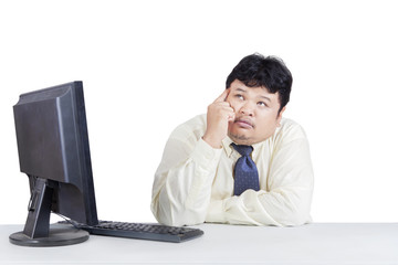 Pensive overweight businessman working with computer