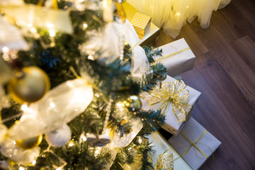Tall christmas tree, beautifully decorated with balls, bows and lights. Lots of christmas gifts under the tree. Wooden floor. Empty space, post card