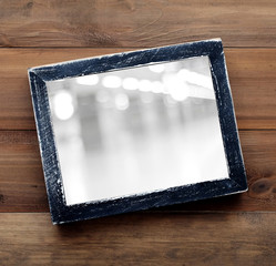 Blur festive bokeh on black wooden frame on wood background