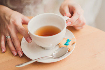 Closeup of bride hands with a cup of tea in cafe. Wedding ring on her finger.