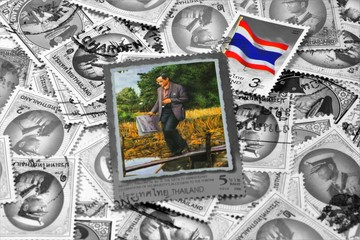 A Thai postage stamp printed in Thailand depicting His Majesty The King Bhumibol Adulyadej and Thailand national flag on black and white stamp background,