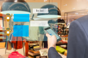 Chatbot concept. Man using  smart phone with virtual chatbopt user interface and greeting message on blur menwear shop background.