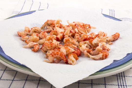 cleaned and cooked crayfish tails with white kitchen paper on a