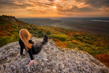 Sunset from the top / A woman on the top of a rock enjoys the view of sunset over an autumn forest