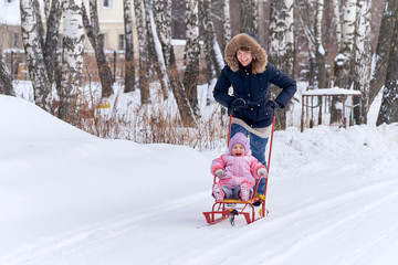 Young mother sledding her crying baby on the snow