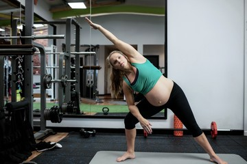 Pregnant woman performing stretching exercise on exercise mat