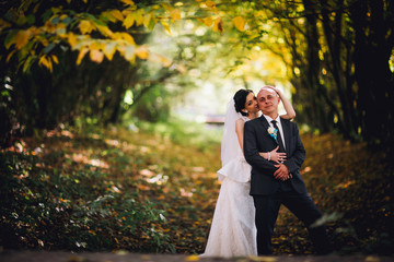 Kissing bride and groom in their wedding day near autumn tree in the forest