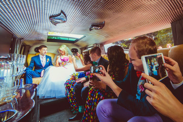 Bridesmaids and groomsmen take pictures of wedding couple sittin