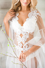 a close picture of a young blonde bride with fine body and wavy hair in a lace white boudoir holding a tight tree bunch and touching her hair. Concept of youth and health.