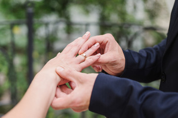 closeup of a groom putting a wedding ring onto the bride's finger during the ceremony