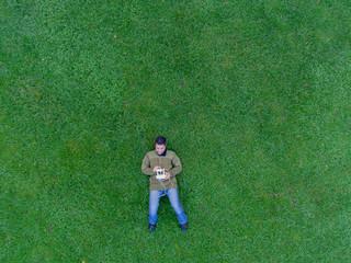 Mann liegt auf Wiese und steuert Flugdrohne per Fernbedienung