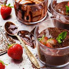 Chocolate mousse with strawberries in glass on rustic table