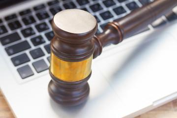Wooden law gawel on laptop keyboard, judgement concept