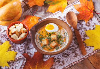 Pumpkin cream-soup decorated with maple leaves, boiled egg and c