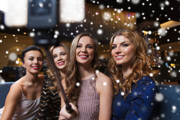 women with smartphone selfie stick at night club