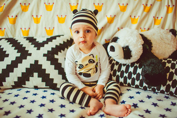 little boy dressed as a panda sitting on a bed
