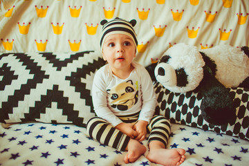 funny little boy dressed as a panda sitting on a bed