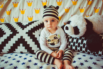 young little  baby sits on a sofa with plush panda