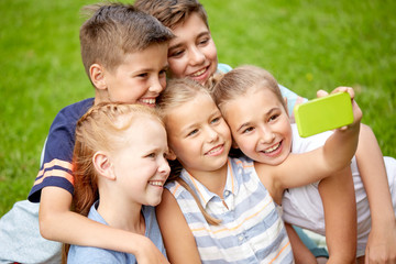 happy kids or friends taking selfie in summer park