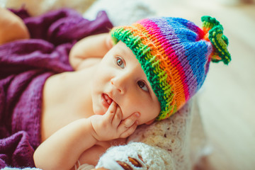 wonderful baby in colorful hat looking at mother