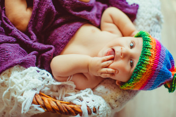 smiling baby lying in a wooden basket