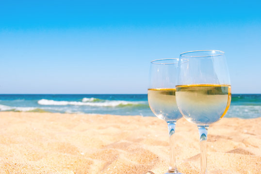 Two glasses of white wine on tropical beach. Romantic idea for couple.