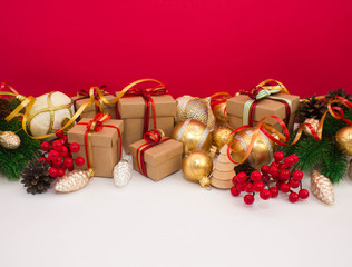 Christmas or New Year background: fur-tree, branches, gifts, colored glass balls, decoration and cones on a red background