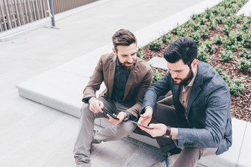 Two casual designer using tablet smartphone