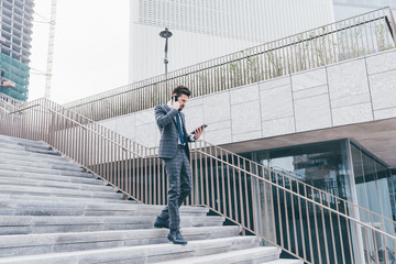 Contemporary businessman multitasking tablet smartphone talking