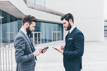 Two contemporary businessman using technological devices
