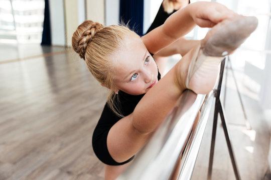 Little dancer stretching legs in dance class